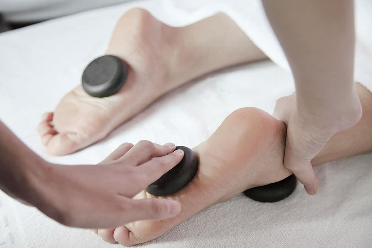 Woman-receiving-hot-stone-foot-massage